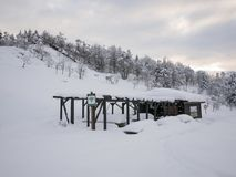 Snowy day in picnic area. OASI ZEGNA, BIELMONTE, ITALY - March 3, 2018: Picnic area in winter snow day with Wi-Fi access point, tables, benches and wooden Stock Photography