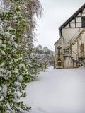 Snowy December churchyard, in Kronenburg, North Rhine-Westphalia, Germany. Snowy December churchyard, Saint John the Baptist Church in Kronenburg, North Rhine stock image
