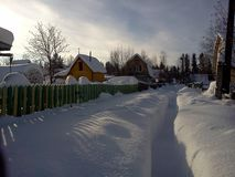 Snowy deep lane in suburban village Stock Photos