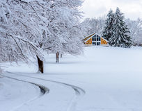 Snowy driveway. A holiday A-Frame home at the end of a snowy driveway lined by snow covered trees Stock Images