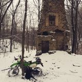 Snowy dual sport ride near building remains Royalty Free Stock Image