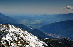 Snowy e creste boscose sopra la città di Jesenice e la valle di Sava Fotografia Stock