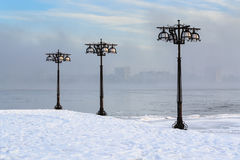 Snowy embankment along the misty river with lanterns at the foggy morning - winter landscape. II Royalty Free Stock Images