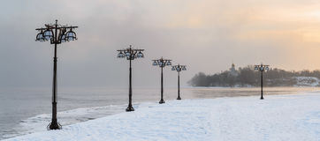 Snowy embankment along the misty river with lanterns at the foggy sunrise - winter landscape. Stock Photos