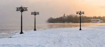Snowy embankment along the misty river with lanterns at the foggy sunrise - winter landscape. II Stock Images