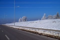 Snowy embankment alongside a motorway. On a cold sunny blue sky winter day with snow covered trees o the skyline in a weather and seasons concept stock image