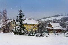 Snowy evening in resort village. Spruce tree on snow covered hill. ski drag lift near the houses. empty gloomy scene Stock Image