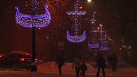 Snowy evening street with passers-by in Christmas illumination in heavy snowfall. stock video footage