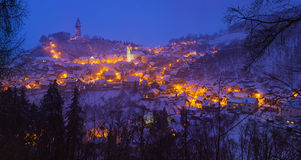 Snowy evening view of the lighted town Royalty Free Stock Image