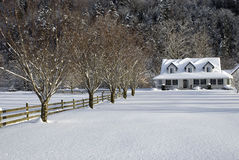 Snowy Farm House. A snow covered country house and open field on a cool winter day stock images