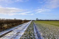 Snowy farm road with hedgerow Stock Photos