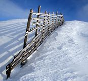 Snowy fence. Delimiter for downhill skiing stock photos