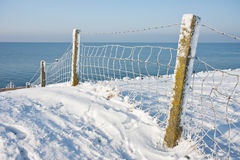 Snowy fence near the coast of the Netherlands. Fence along the near the snowy coast of the Noordoostpolder; the Netherlands royalty free stock image