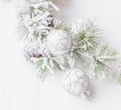 Snowy festive pine branch with silver and white balls decoration. S royalty free stock image