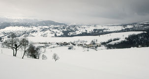Snowy fields and mountains, and a little rural town Stock Image