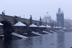 Snowy foggy Prague Old Town with Bridge Tower and St. Francis of Assisi Cathedral from Charles Bridge with its baroque Statues Stock Photos