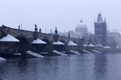 Snowy foggy Prague Old Town with Bridge Tower and St. Francis of Assisi Cathedral from Charles Bridge with its baroque Statues Royalty Free Stock Photography