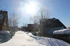 Snowy footpath. Along the silent houses and trees on a sunny day stock photo