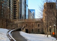 Snowy footpath bending away from the riverwalk in downtown Chicago Loop stock photos