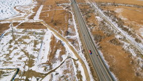 Snowy and frozen winter road with a moving car on it. stock footage