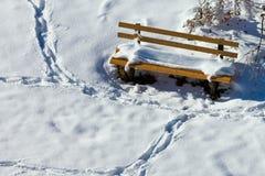 Snowy-Fuß druckt um Schnee bedeckte Parkbank Stockbild