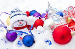Snowy and funny. Snowman, baubles, confetti and Christmas tree on white snow stock images