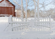 Snowy gate and red barn in the background a winter day Royalty Free Stock Photography