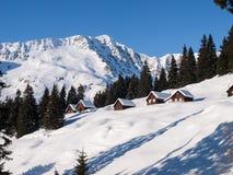 Snowy-Gebirgschalet im Holz Stockfotografie