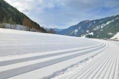 Snowy-Gebirgslandschaft mit Querlandspur Stockfotos