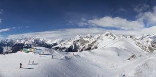 Snowy-Gebirgsspitzen-Skiortpanorama Lizenzfreie Stockfotos