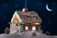 Snowy gingerbread cottage with stars and moon Royalty Free Stock Photos