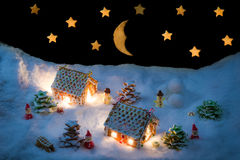 Snowy gingerbread village with stars and moon Stock Photos