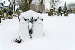 Snowy Grave. Snow covered grave with the crucified Jesus on a snowy graveyard stock image