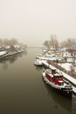 Snowy Harbour. Grey skies and still water in a winter harbor view Royalty Free Stock Images