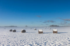 Snowy hay bales with fog Royalty Free Stock Images