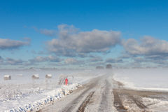 Snowy hay bales with road in fog Royalty Free Stock Image