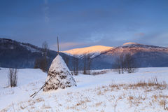 Snowy haystack on the background of the Carpathian Mountains Stock Image