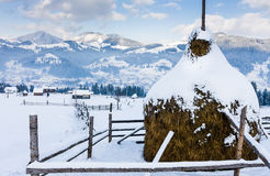 Snowy haystack on a background of a village in the mountains Stock Photos