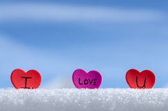 Snowy Hearts Blue sky. Colorful paper & felt heart Valentines background in the snow Royalty Free Stock Images