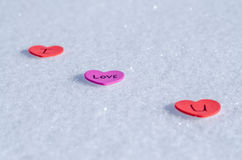 Snowy Hearts. Colorful paper & felt heart Valentines background in the snow Stock Photography