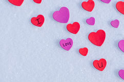 Snowy Hearts. Colorful paper & felt heart Valentines background in the snow Royalty Free Stock Photos