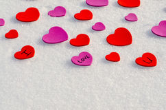 Snowy Hearts. Colorful paper & felt heart Valentines background in the snow Royalty Free Stock Images