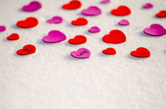 Snowy Hearts. Colorful paper & felt heart Valentines background in the snow Royalty Free Stock Image