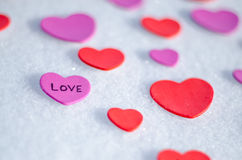 Snowy Hearts. Colorful paper & felt heart Valentines background in the snow Stock Images