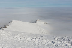 Snowy high mountains and clouds. View from the top of the mountain. Royalty Free Stock Images
