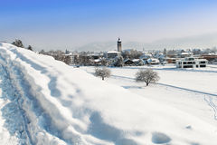 Snowy hill in front of village Royalty Free Stock Photos