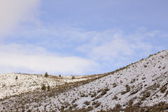 Snowy Hill Ridge Under Blue Skies and Clouds Royalty Free Stock Images