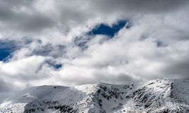 Snowy hills and clouds on the sky. Snowy hills in Low Tatras mountains. Winter peaks landscape and clouds on the sky royalty free stock photos
