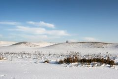 Snowy hills in the winter. Snowy hills in winter with blue sky and clouds Stock Image