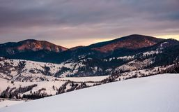 Snowy hillside in mountains at sunrise Stock Photos
